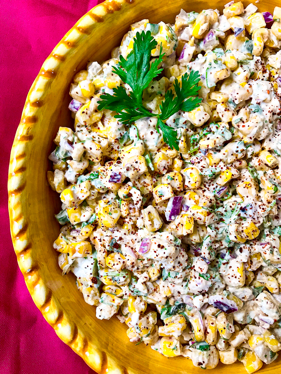 A yellow bowl of Mexican street corn salad.