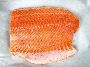 A raw salmon fillet sprinkled with salt and pepper.