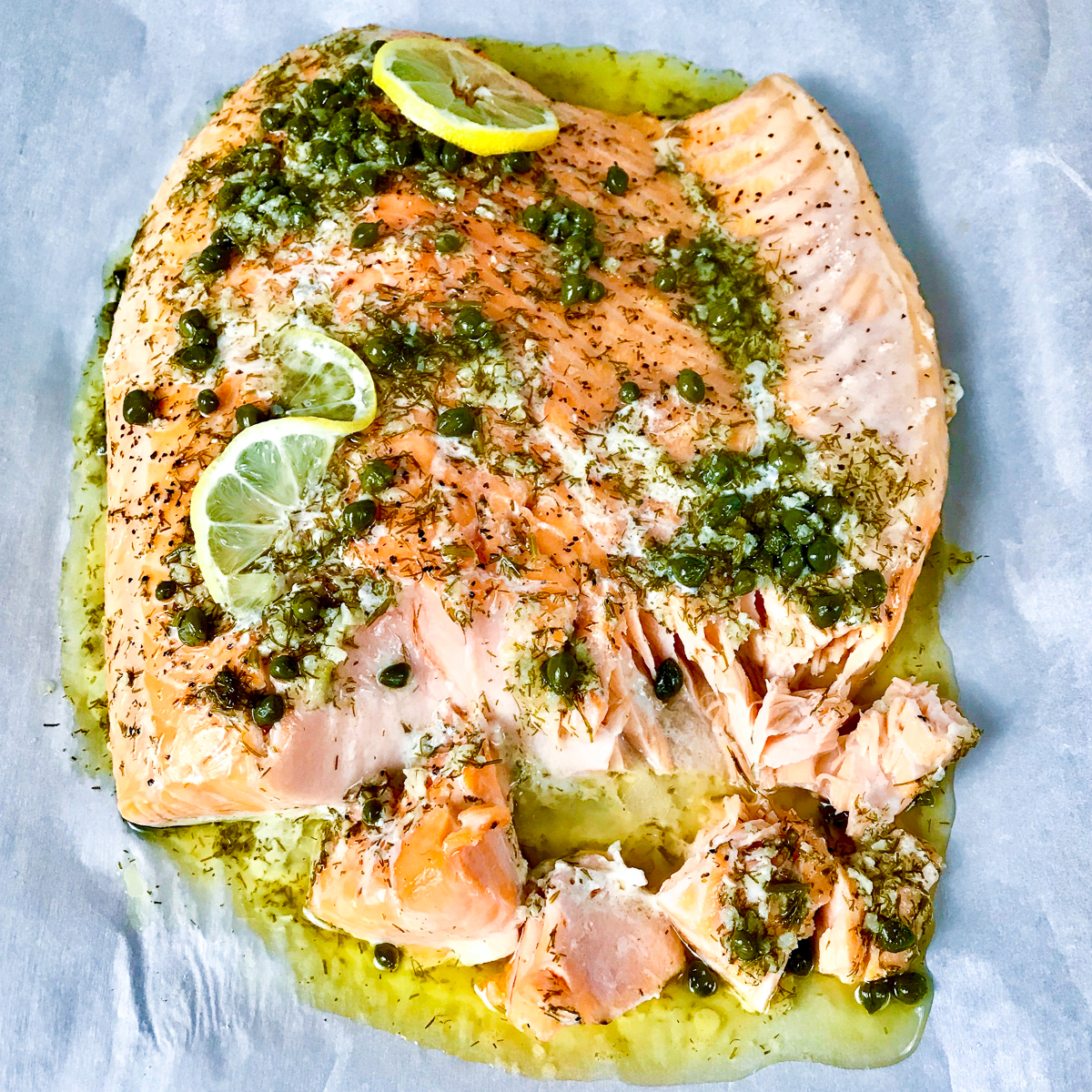 Slow roasted salmon topped with herbs and lemon on a baking sheet.