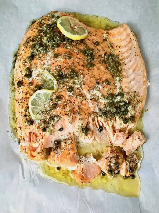 Slow Roasted Salmon with Lemon Caper Butter topped with sliced lemons.