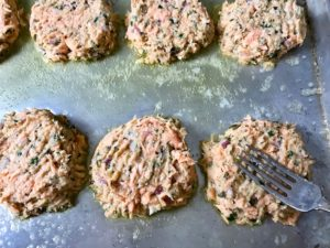 Flattening salmon cakes with a fork.