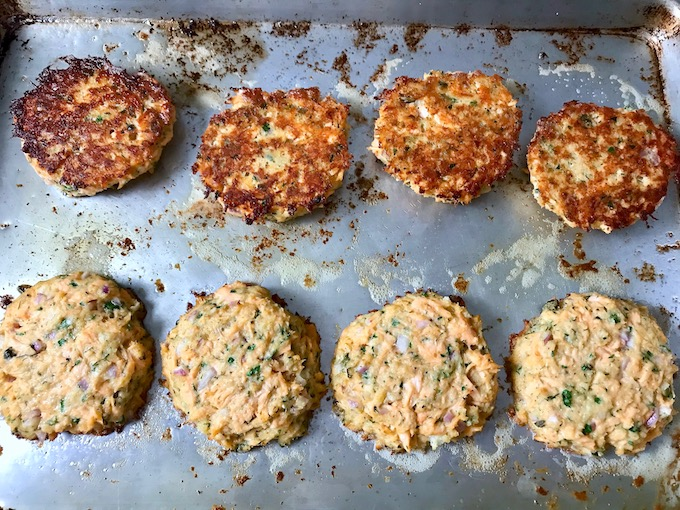 Flipping salmon cakes on a baking sheet.