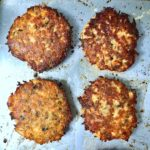 Roasted crispy salmon cakes on a baking sheet.