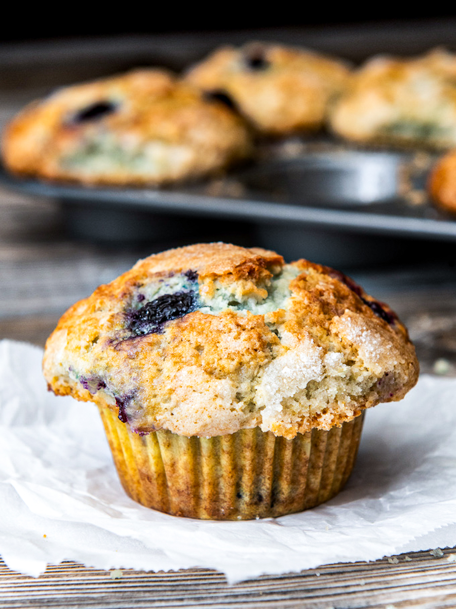 A blueberry muffin with a pan of muffins in the background.