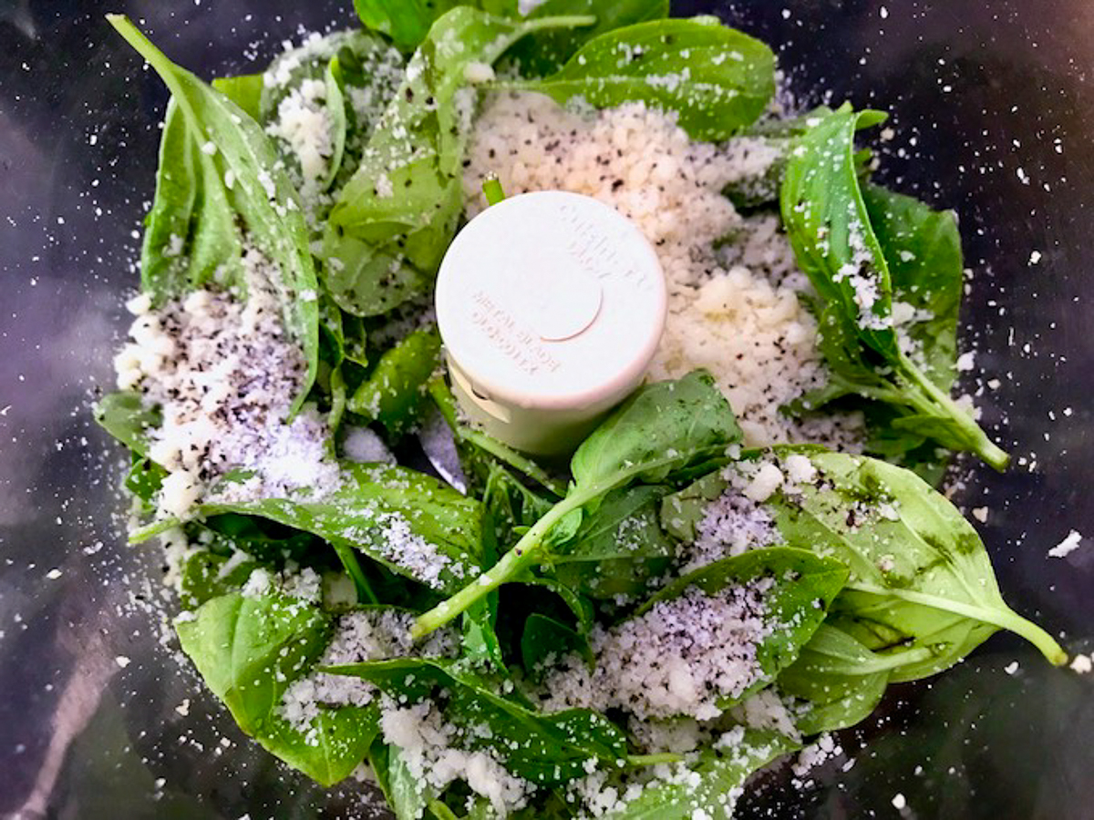 Italian pesto ingredients in food processor bowl.
