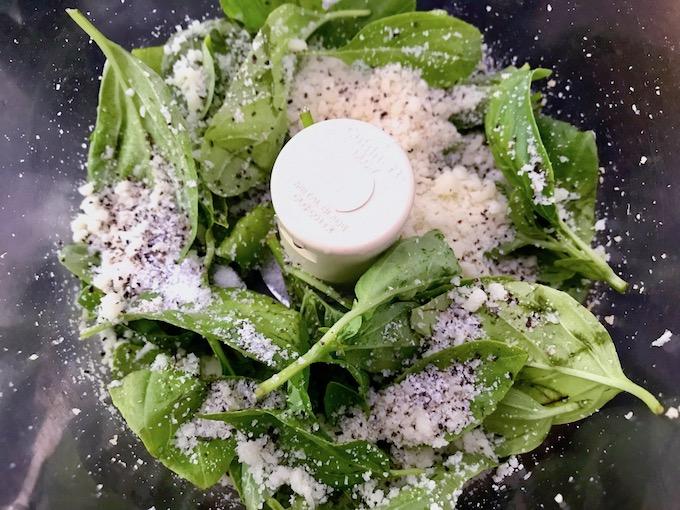 Italian pesto ingredients in food processor bowl.