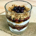 A glass of blueberry parfait showing layers of yogurt, blueberries, and granola.