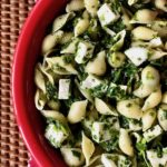 A red bowl with spinach and cheese pasta salad.