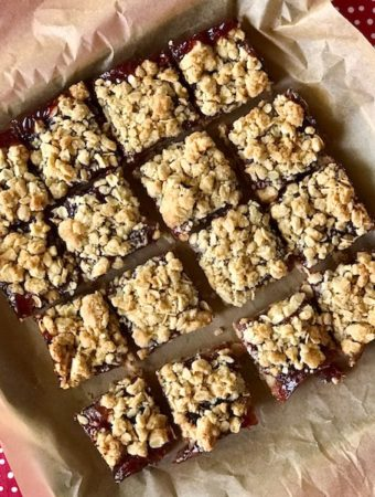 Sliced strawberry jam bars on parchment.