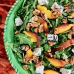 A bowl of grilled peach and arugula salad with blue cheese.