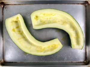 A zucchini halved lengthwise drizzled with olive oil.