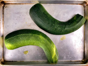 A large zucchini cut side down on a baking sheet.