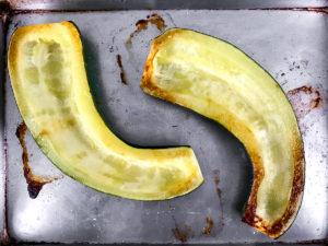 An unstuffed roasted zucchini on a baking sheet.