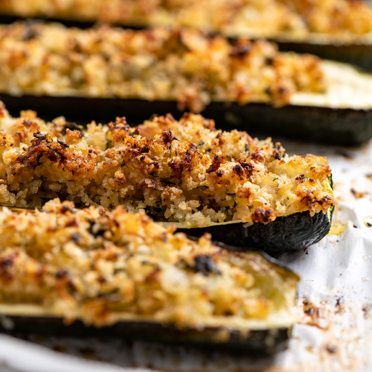 Golden brown roasted stuffed zucchinis on a baking sheet.