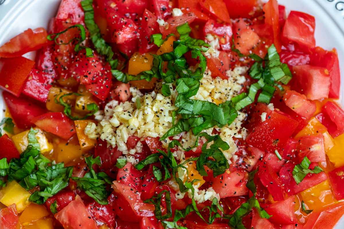 Chopped tomatoes, minced garlic, and julienned basil in a bowl.