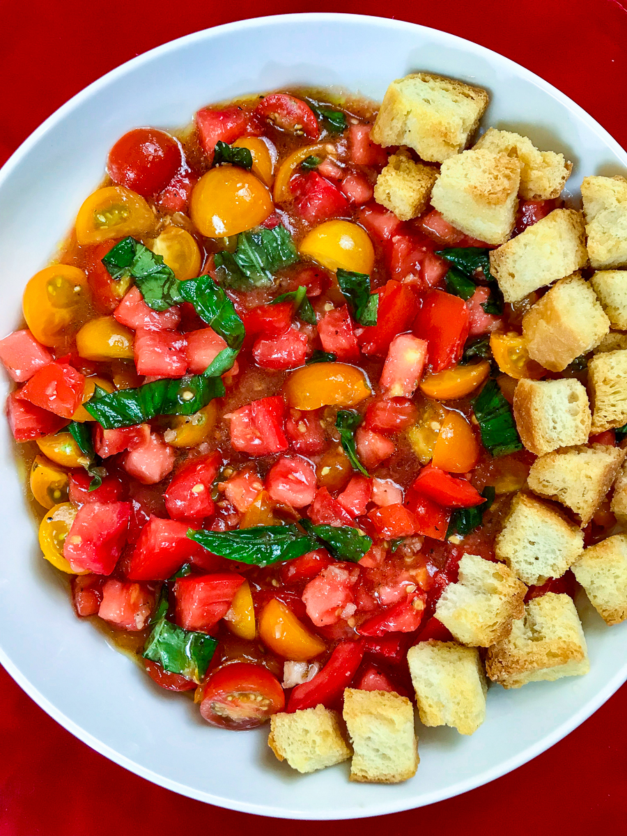 Tomato salad with toasted croutons on one side.