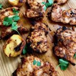 Grilled chipotle chicken with grilled peaches on a cutting board.