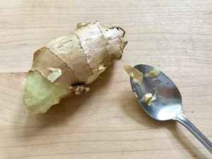 Ginger peeled with a spoon on cutting board.