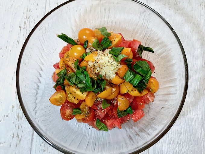 Chopped tomatoes, minced garlic, and torn basil leaves in a bowl.