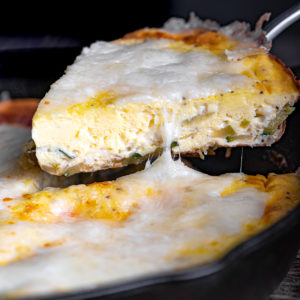 A slice of zucchini frittata being lifted from skillet.