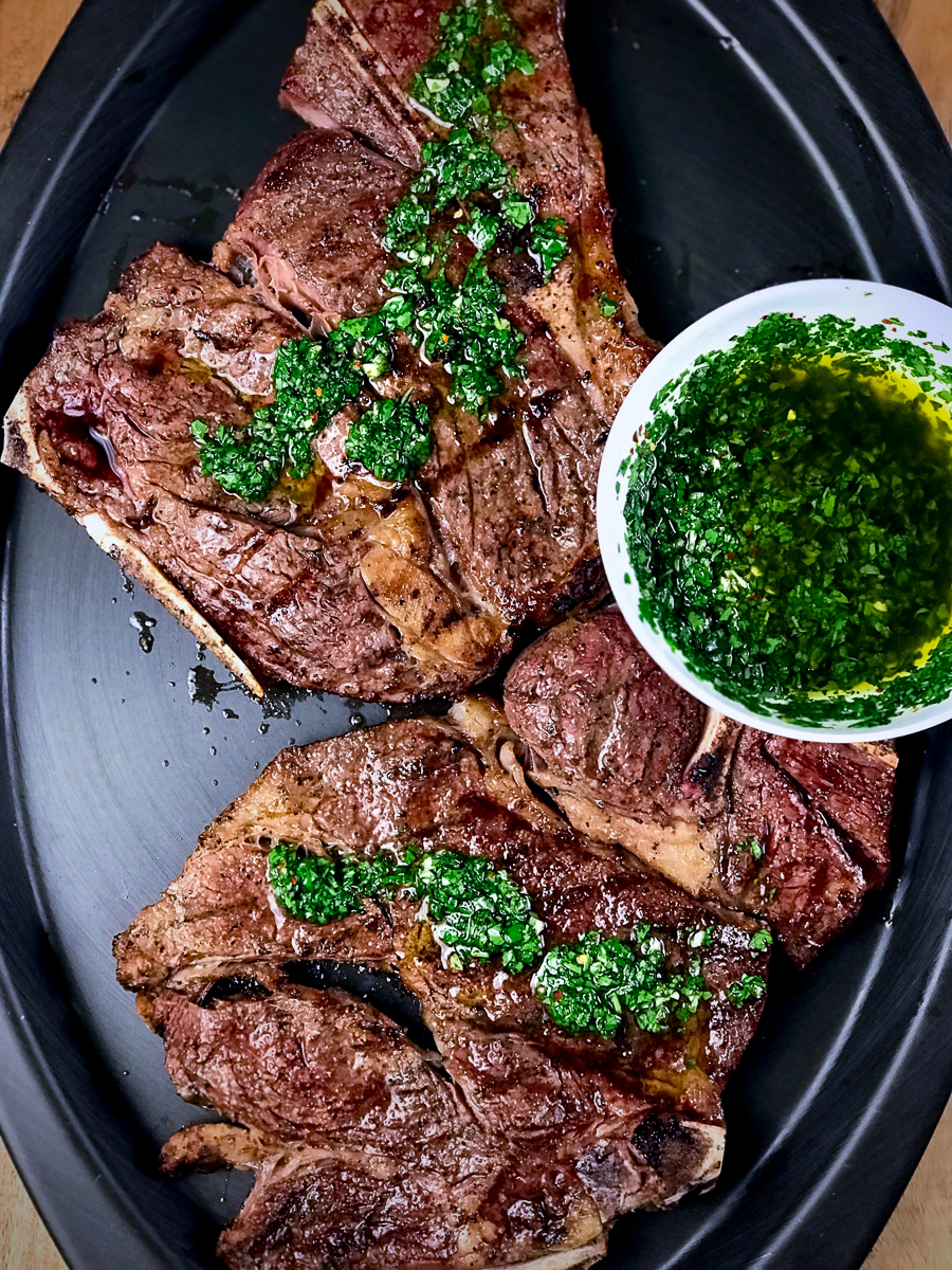 Two chuck steaks coated with chimichurri sauce.