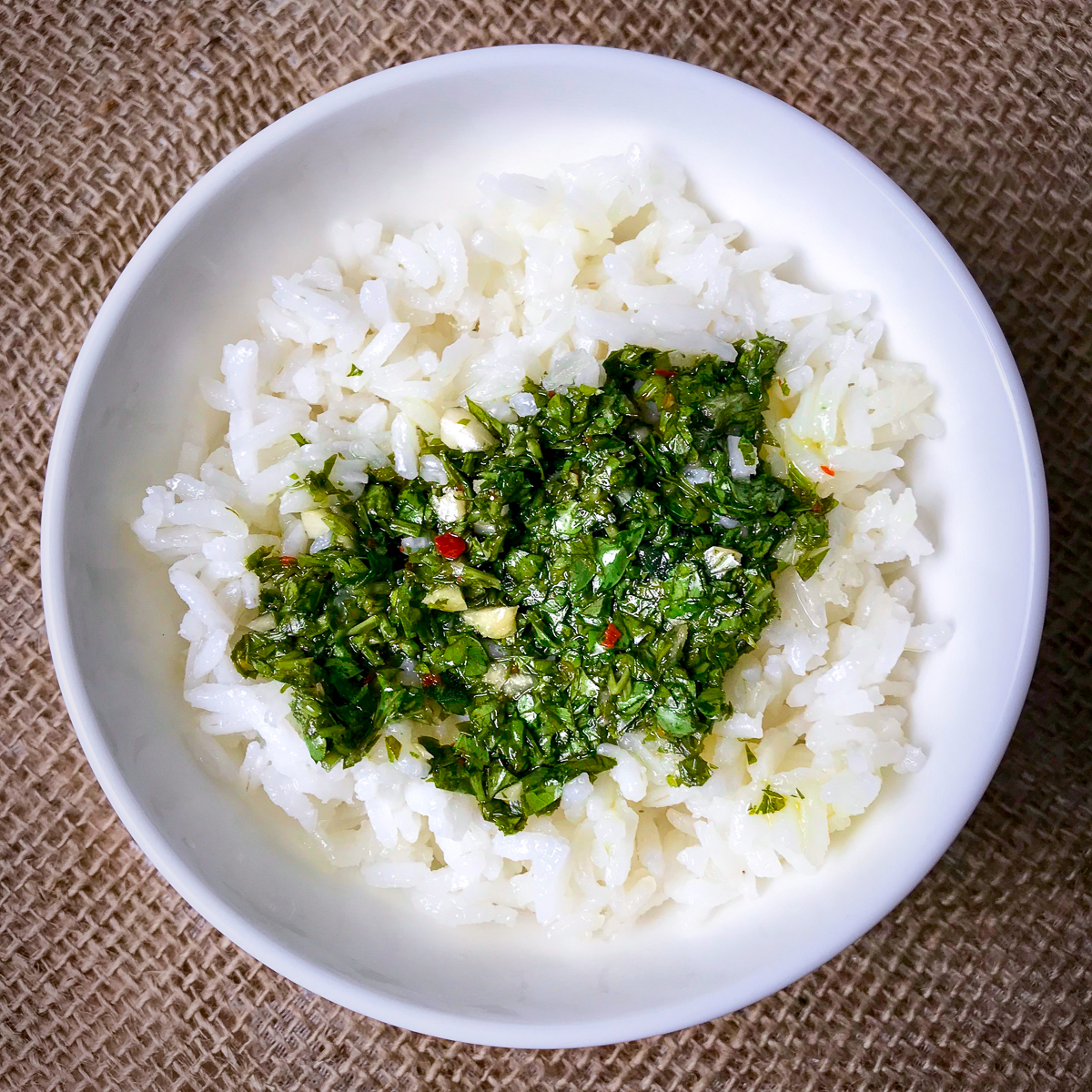 A white bowl of rice topped with some chimichurri sauce.