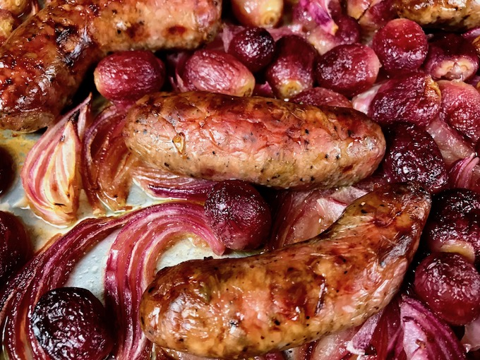 A closeup of roasted sausages, onions, and grapes.