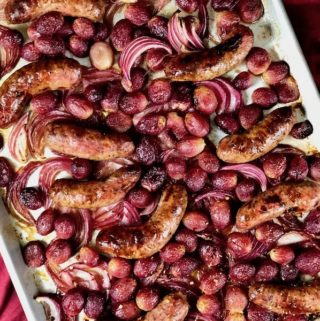 Roasted sausages and grapes on a baking sheet.