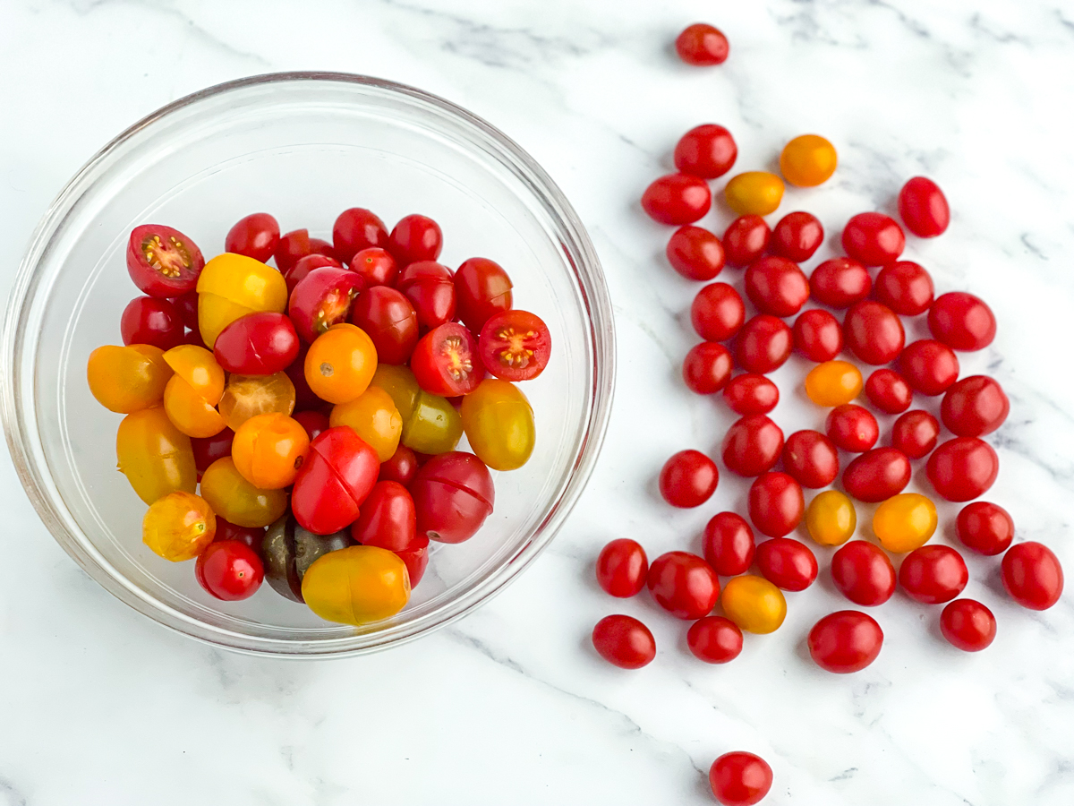 Cherry tomatoes in a bowl with some scattered on a counter.