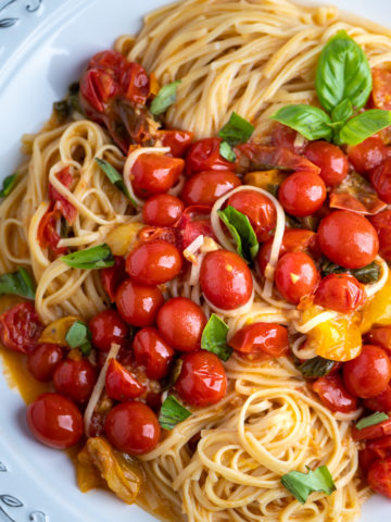 A platter of sautéed tomatoes with angel hair pasta.