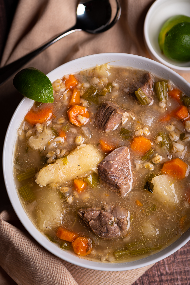 A bowl of beef barley soup in a white bowl with a lime wedge.