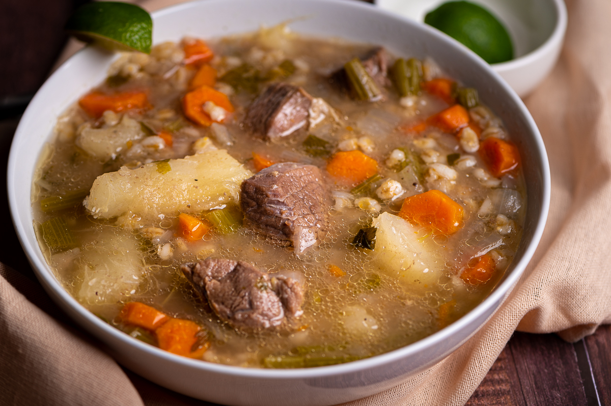 Angle view of a bowl of beef barley soup in a white bowl.