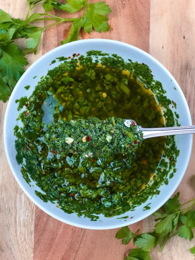 A bowl of fresh chimichurri sauce.