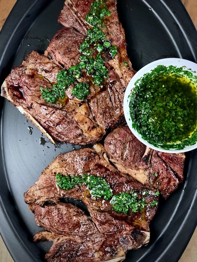 Grilled chuck steaks with chimichurri sauce on top.