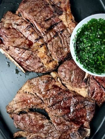 Grilled 7-bone chuck steaks on a platter with a bowl of chimichurri.
