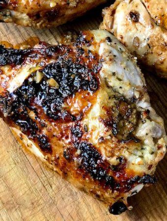 Broiled mustard garlic chicken breasts on a board.