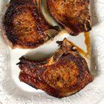Pan seared pork chops on a platter.