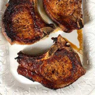 Pan seared pork chops on a platter.