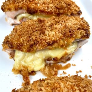 Baked chicken cordon bleu on a platter with cheese oozing out.