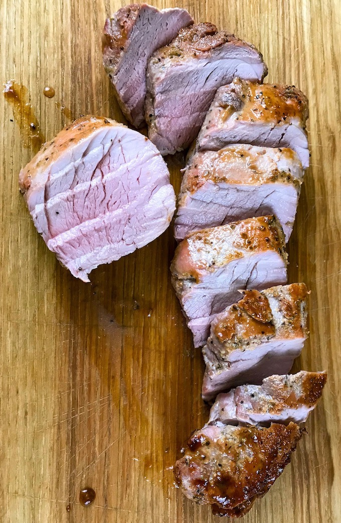Sliced maple glazed pork tenderloin on a board.