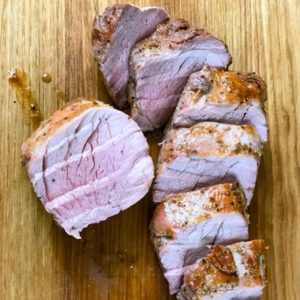 Sliced maple glazed pork tenderloin on a board.
