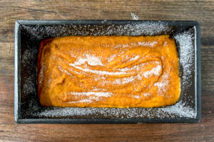 Pumpkin bread batter in a loaf pan topped with sugar.