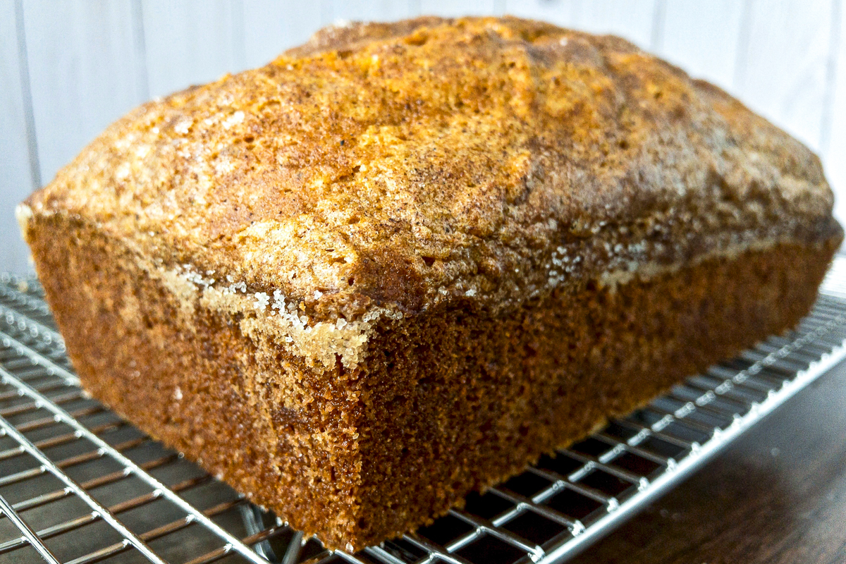 A loaf of pumpkin bread cooling on a rack.