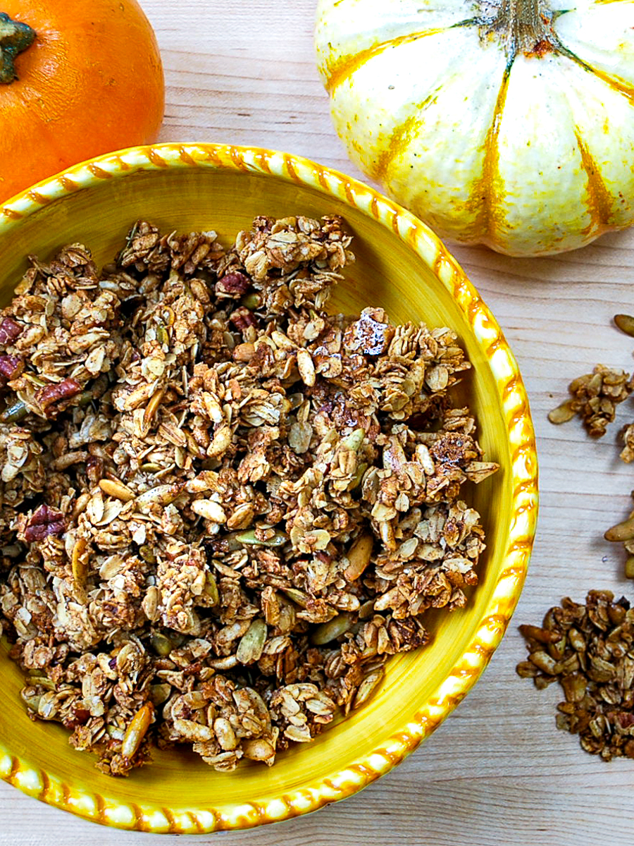 A yellow bowl filled with pumpkin spice granola with two small pumpkins next to it.