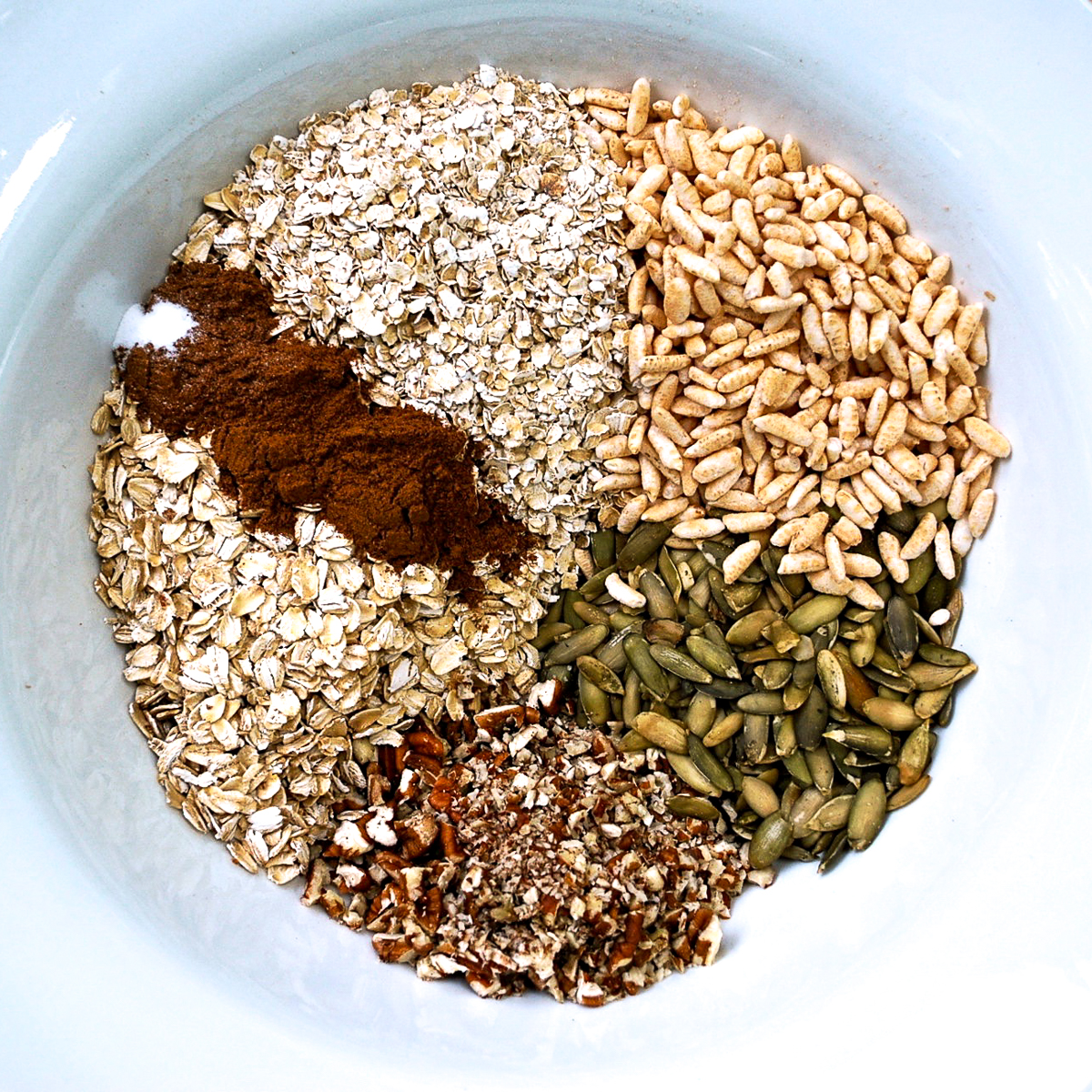 Dry ingredients for pumpkin spice granola in a while bowl.