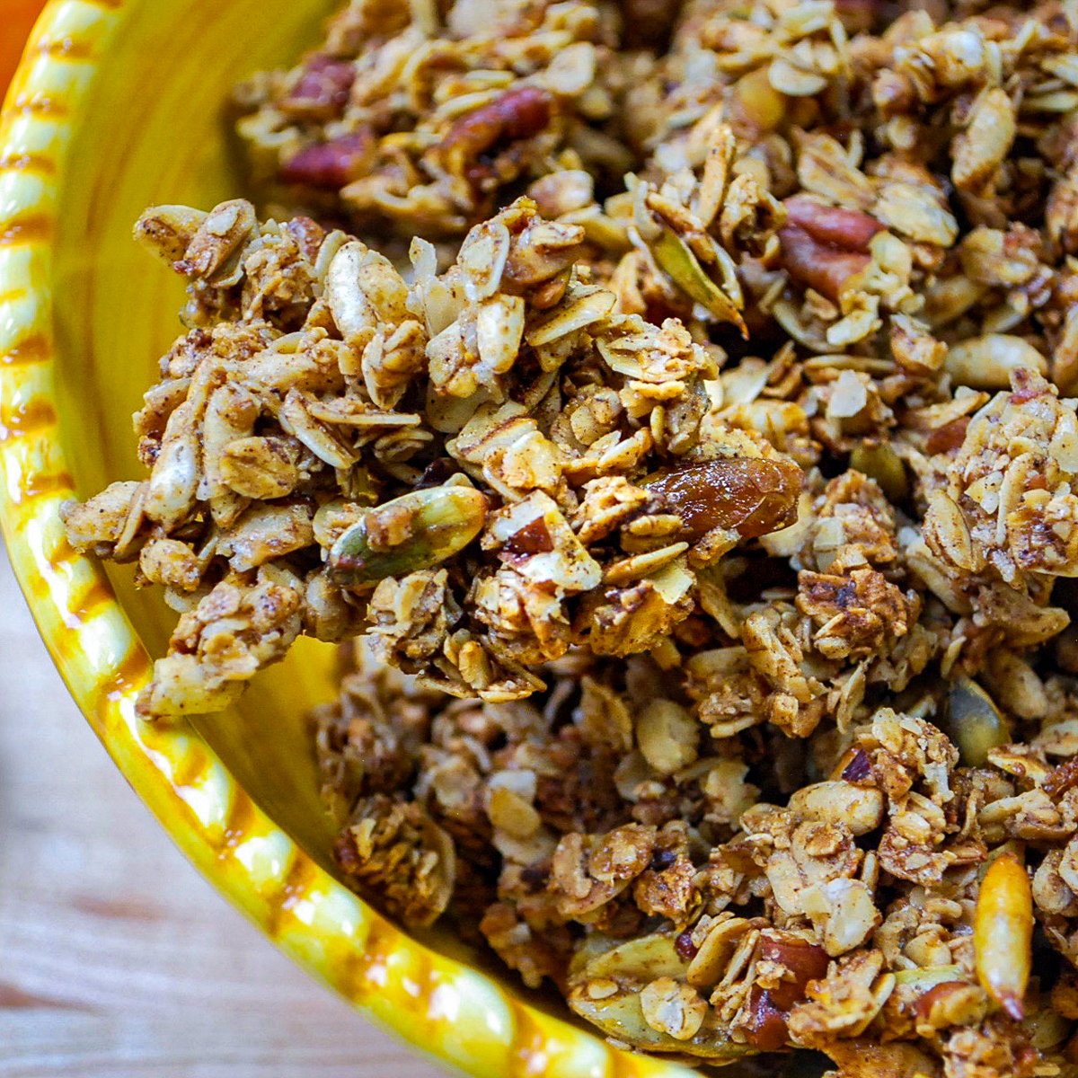 A closeup of a yellow bowl filled with granola.