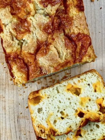 Cheddar bread sliced on a board.