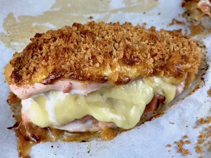 Baked chicken cordon bleu on a baking sheet with cheese oozing out.