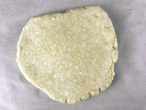 A disc of pie crust on parchment paper.