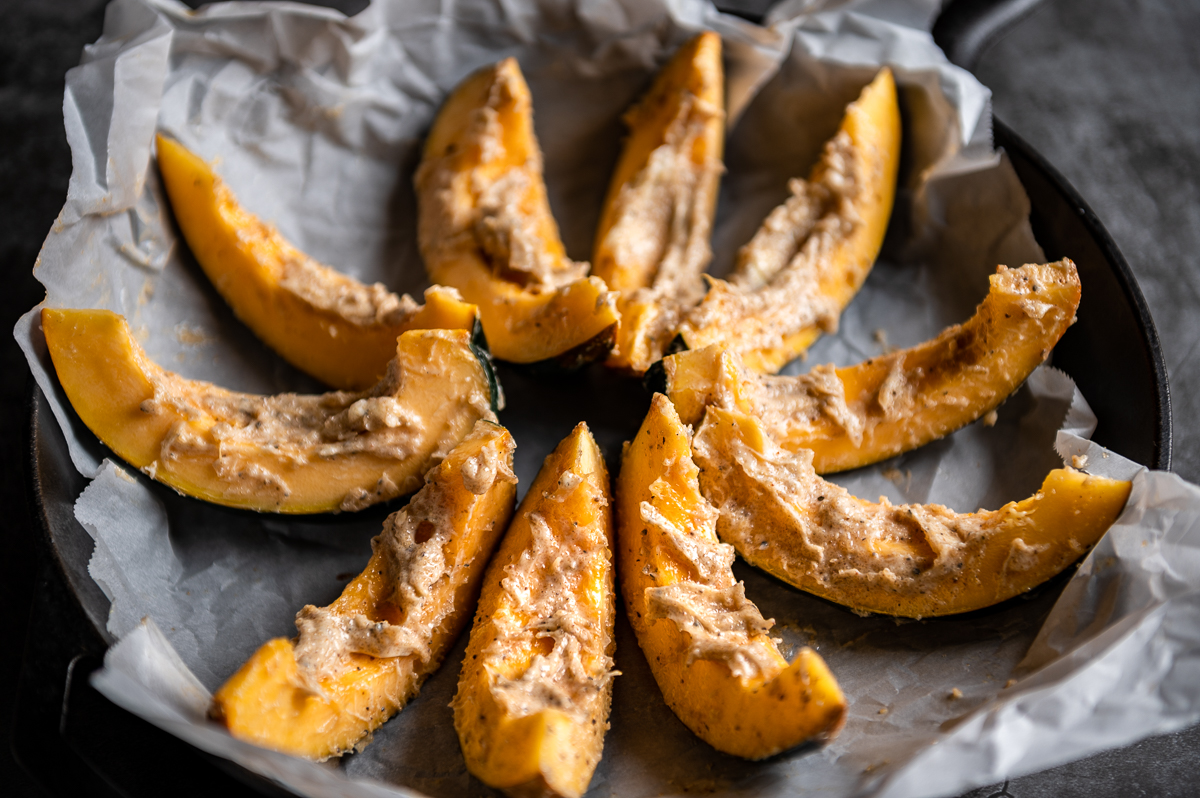 Acorn squash wedges spread with spiced butter in a cast iron skillet.